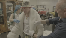 Hip Hop stylist Whitney Middleton and Jonathan Warren help Macklemore try on a Liberace Museum Collection piece.